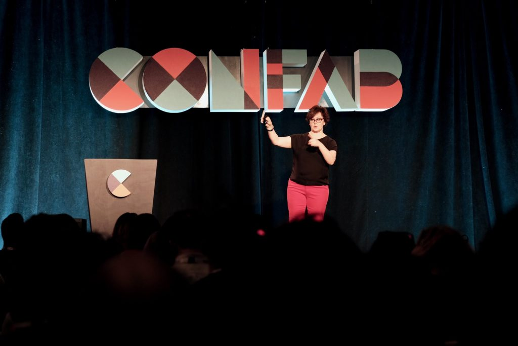 Kristina Halvorson raising her hand on stage with Confab 2019 letters behind her